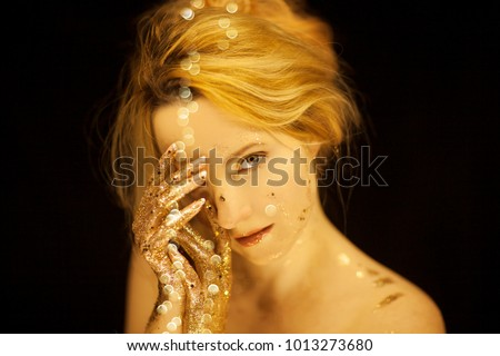 Beautiful woman in gold, golden hands, glitter sensual glamour studio shoot