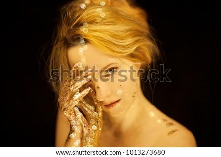 Beautiful woman in gold, golden hands, glitter sensual glamour studio shoot