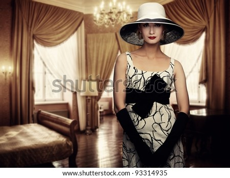 Beautiful woman in hat in luxury room