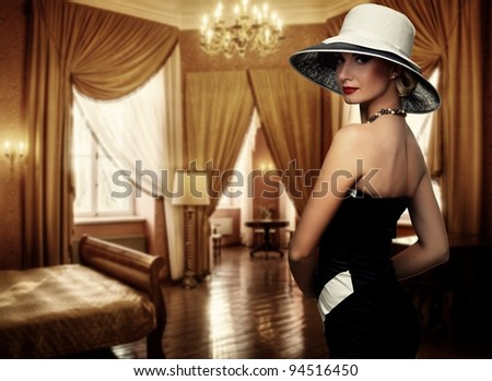 Beautiful woman in hat in luxury room.