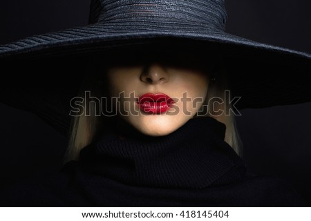 Beautiful woman in hat. Retro fashion.summer hat with large brim over dark background