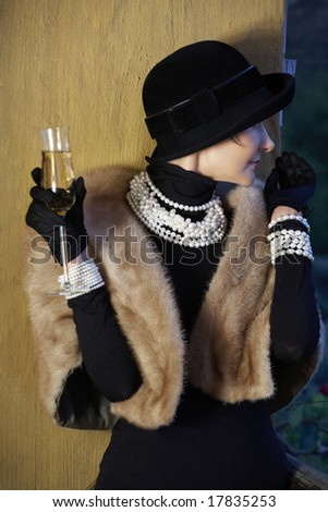 beautiful woman in her mid 40s with blond short hair in a fur stole wearing fresh water pearls and holding a glass of champagne - stock photo
