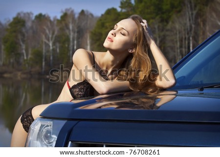 Beautiful woman in lingerie standing by the car and enjoy the sunshine and good weather