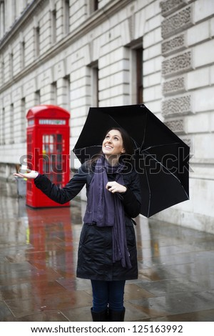Beautiful woman in London in a rainy day, holding an umbrella
