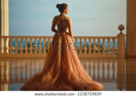 Beautiful woman in luxurious ballroom dress with tulle skirt and lacy top standing on the large balcony with sea view. Back view Stok fotoğraf ©