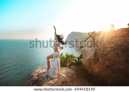 Beautiful woman in oriental dance costume on the mountains by the sea dances after sunset #694418149
