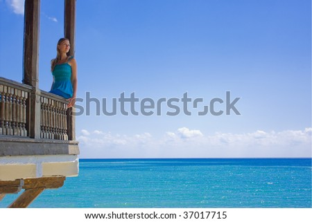 Beautiful woman in paradise on a balcony