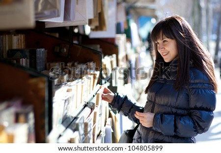 Beautiful woman in Paris selecting a book in an outdoor bookseller box