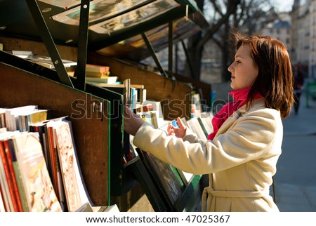 Beautiful woman in Paris selecting a book in an outdoor bookseller box stock photo