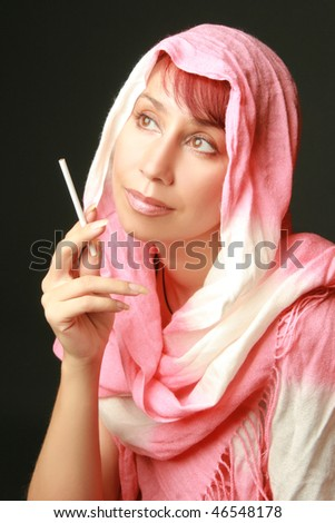Beautiful woman in pink shawl with a cigarette on black background.