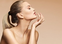 Beautiful woman in profile touching her lips. Photo of woman finishes makeup on beige background. Youth and skin care concept