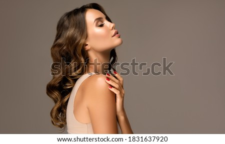 Beautiful woman in profile  with long  and   shiny wavy  hair .  Beauty  model girl with curly hairstyle .