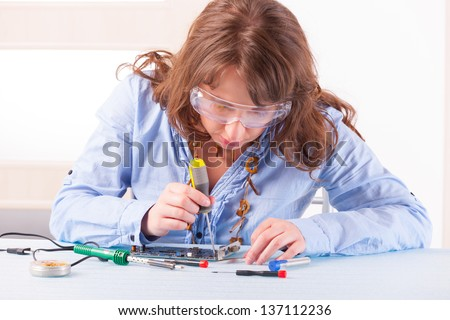 Beautiful woman in protective glasses fixing computer parts with screwdriver and soldering iron