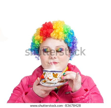 Beautiful woman in rainbow clown wig and creative rainbow make-up holding cup of tea and breathing in the steam at white background. Free space for text