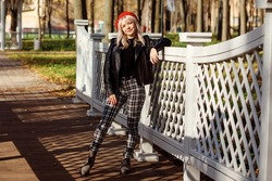 Beautiful woman in red beret, black leather jacket, checkered trousers spending time outdoor in fall