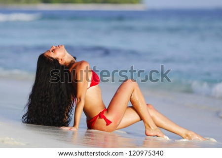 Beautiful woman in red bikini on beach