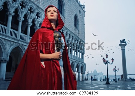Beautiful woman in red cloak against Dodge's Palace