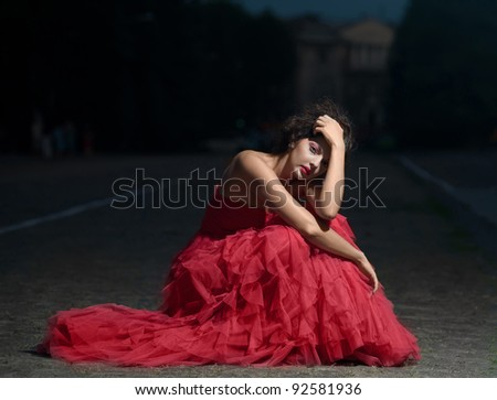Beautiful woman in red dress at sunset