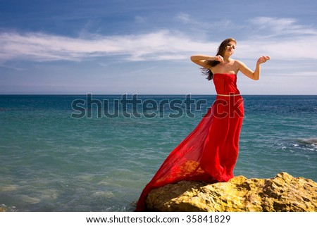 Beautiful woman in red dress at the sea beach