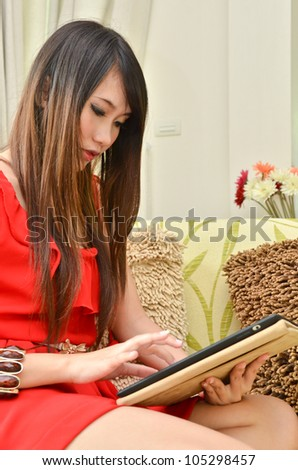Beautiful woman in red dress resting on a sofa while playing with a tablet in living room - stock photo