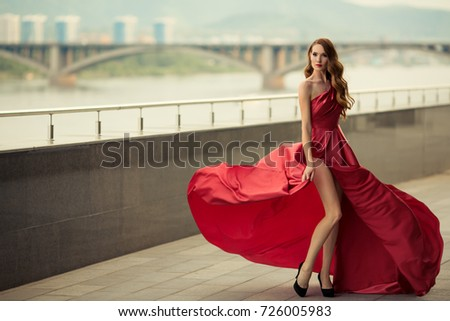 Stock Photo Beautiful woman in red fluttering dress. Urban background.