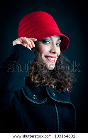 Beautiful woman in red hat against black background. Retro portrait
