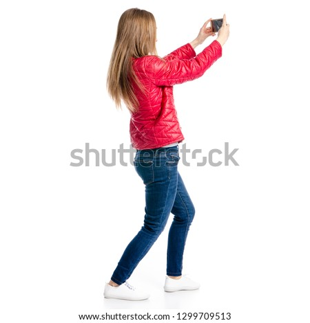 Beautiful woman in red jacket and jeans in hand smartphone selfie on white background isolation, back view