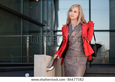 Beautiful woman in red jacket going to shops