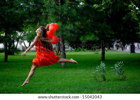 Beautiful woman in red jumping in park
