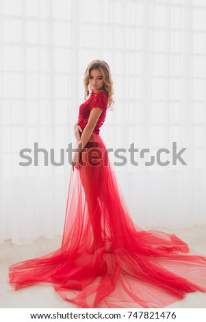 Beautiful woman in red negligee dress in front of the window  c07548de6