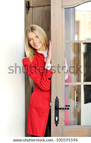 Beautiful woman in red suit looks out the door