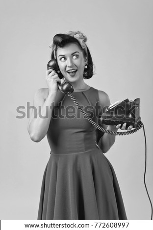 Beautiful woman in retro style with perfect hair and make up , speaking via vintage phone.