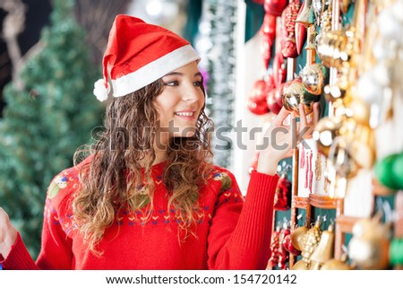 Beautiful woman in Santa hat buying Christmas ornaments at store