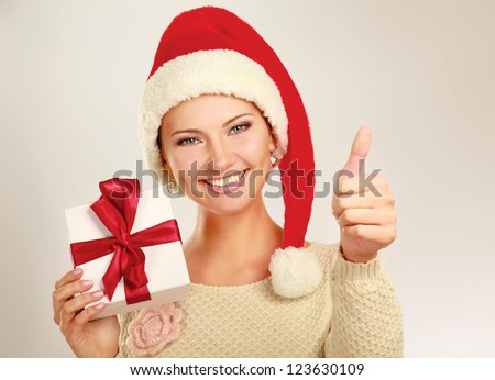 Beautiful woman in santa hat  holding gift and showing ok , isolated on white background