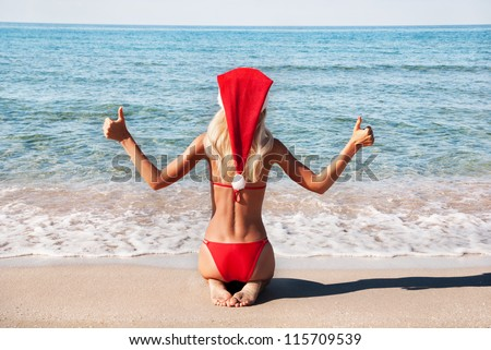 Beautiful woman in santa hat on the sea shore - winter holiday in the hot countries concept