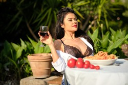beautiful Woman in summer dress eats Italy spaghetti pasta with meat and wine in Italy house garden