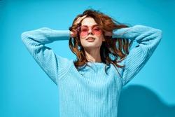 Beautiful woman in sunglasses in blue sweater