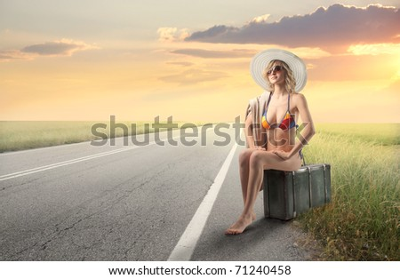 Beautiful woman in swimsuit sitting on a suitcase on a countryside road