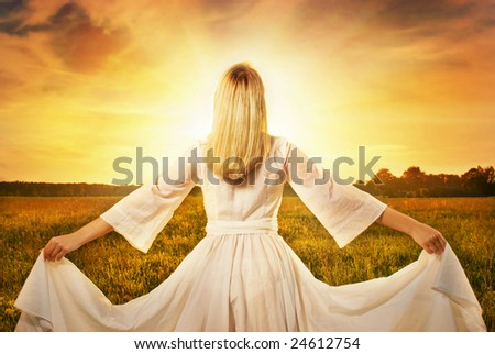 Beautiful woman in the field at sunset