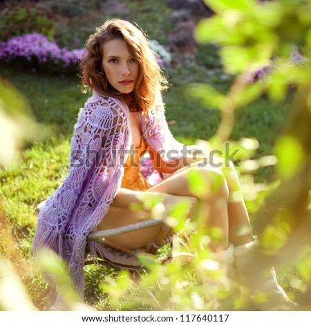 beautiful woman in the garden in sunny day sitting in the chair