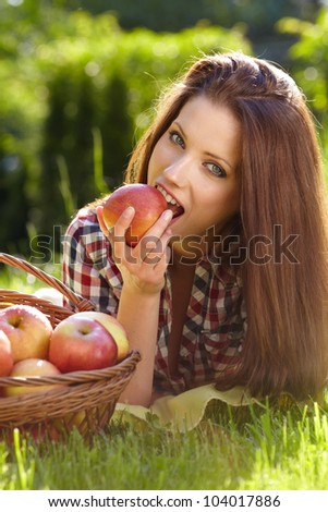 Beautiful  woman in the garden with apples #104017886