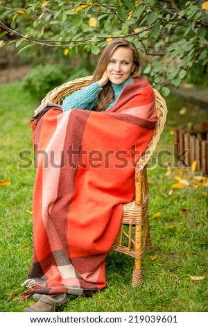 Beautiful woman in the garden wrapped in a plaid blanket sitting in armchair