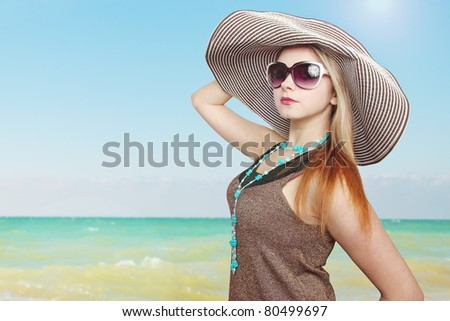 Beautiful woman in the hat near the sea