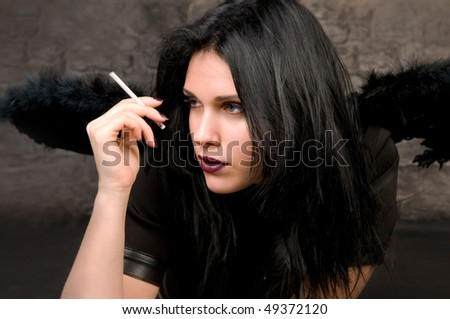 Beautiful woman in the image of a black angel with a cigarette in his hand.