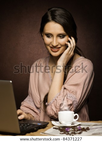 Beautiful woman   in the kitchen while working on laptop and having coffee