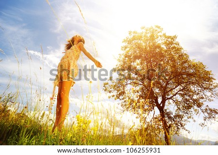 Beautiful woman  in the midst of a green lawn, she looks at the sky, so carefree