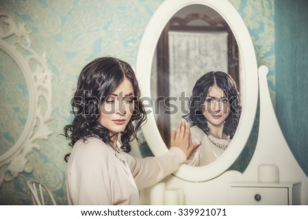 Beautiful woman in the mirror reflected the smiles magically in retro interior #339921071