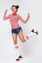 Beautiful woman in the roller-skates and with red headphones and lollipop in studio