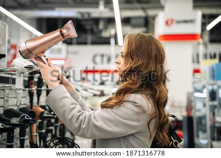 Beautiful woman in the store is testing a hairdryer. Foto stock ©