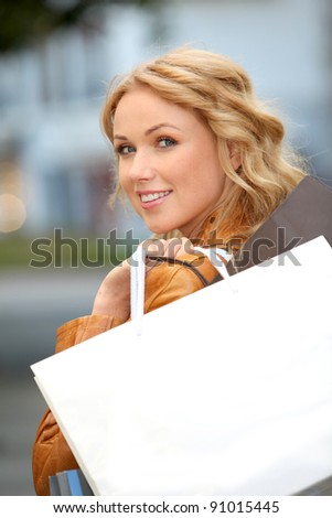 Beautiful woman in town holding shopping bags